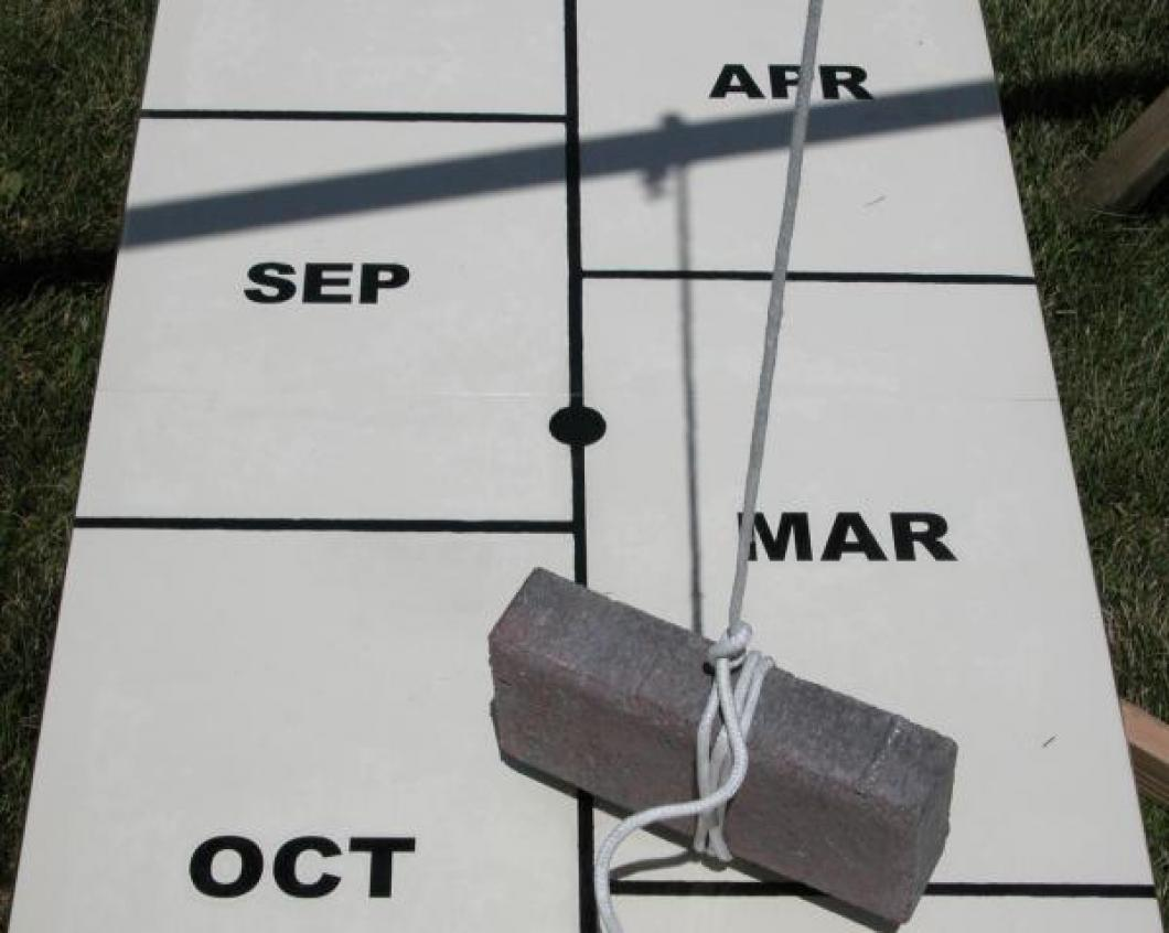 Closeup aligning human sundial centre board with shadow of cord at exact time