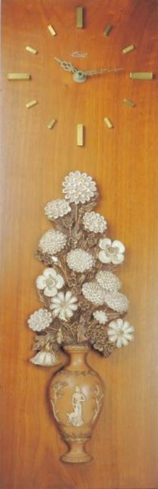 """A vertical format wood panel wall clock with chalkware flowers in a vase, 29"""" H (museum collection)"""
