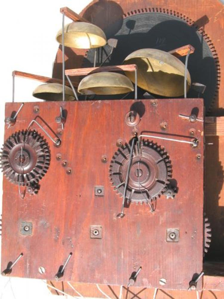 The back of the wood movement, showing the wood hour-strike count wheel and wood quarter-hour bells strike wheel.