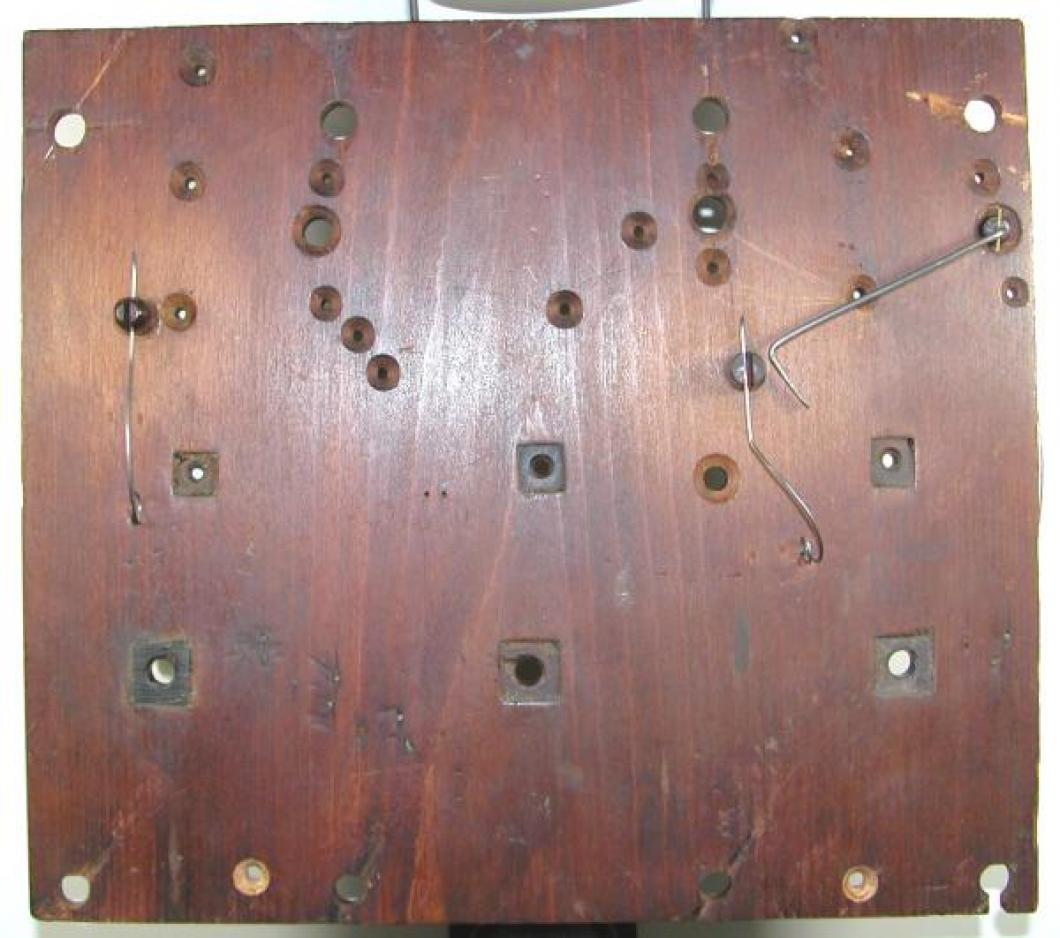 The OUTSIDE of the wood FRONT plate; note the square lignum vitae bushings.