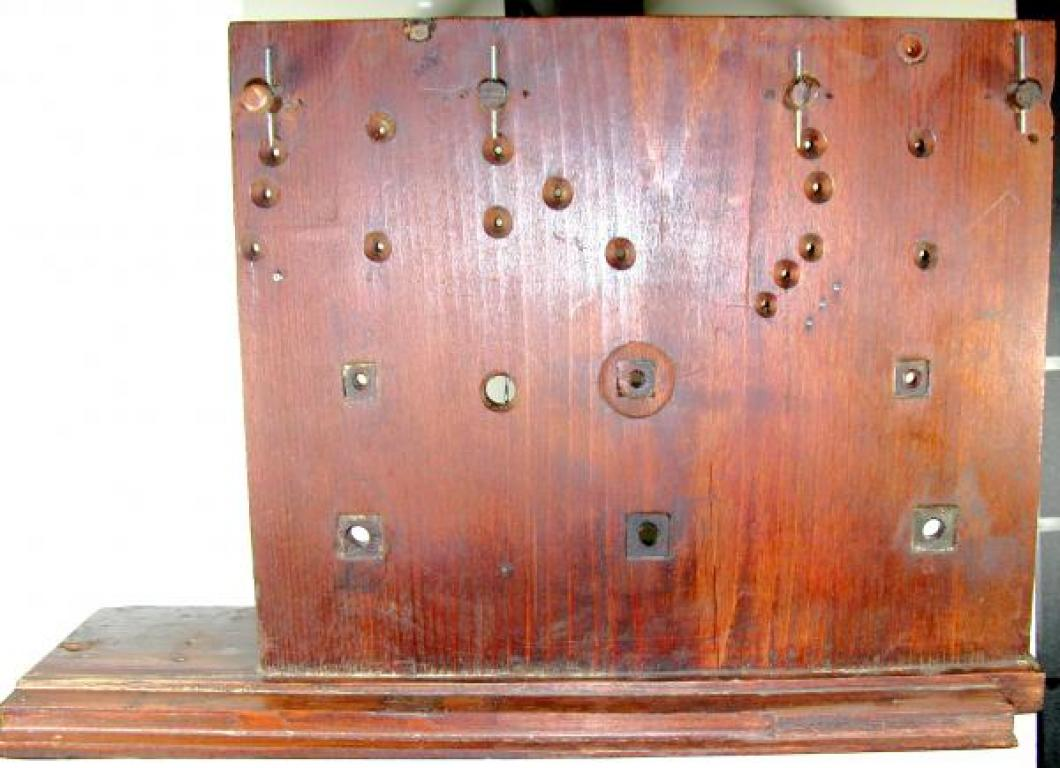 The OUTSIDE of the wood BACK plate; note the square lignum vitae bushings