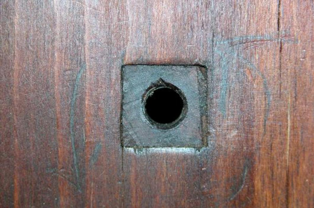 Close-up of one of the square lignum vitae bushings; two sizes are found in both wood plates, visible both sides