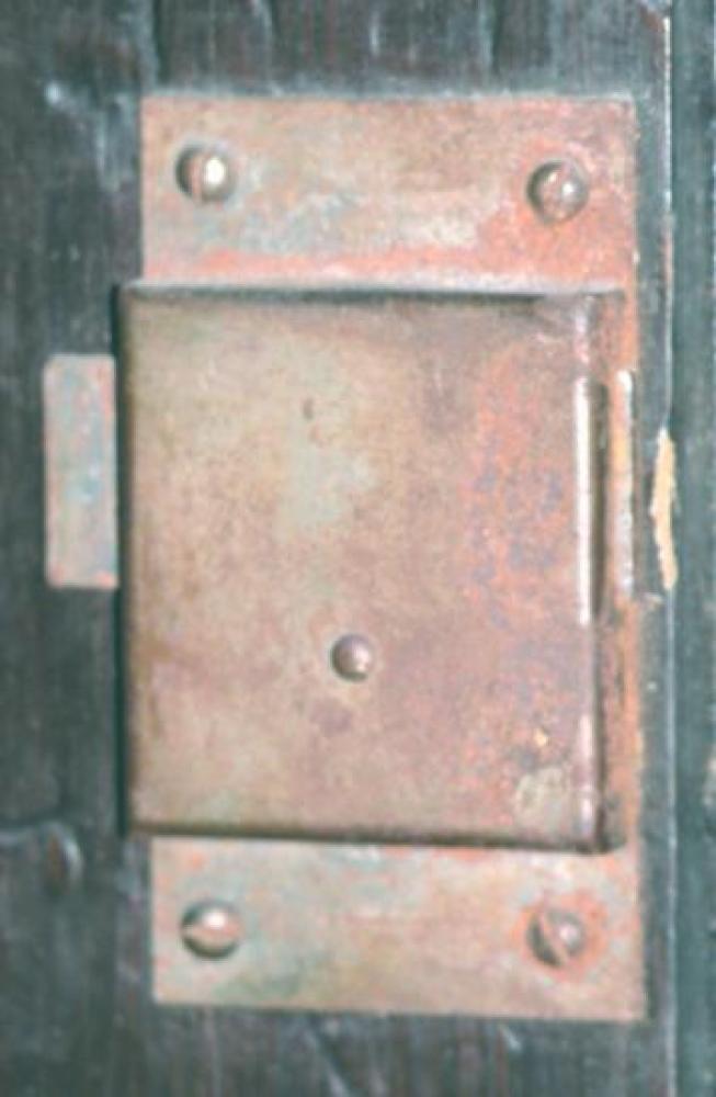 The rusty lock inside the pine wood door (with the original key, door edge to the right).