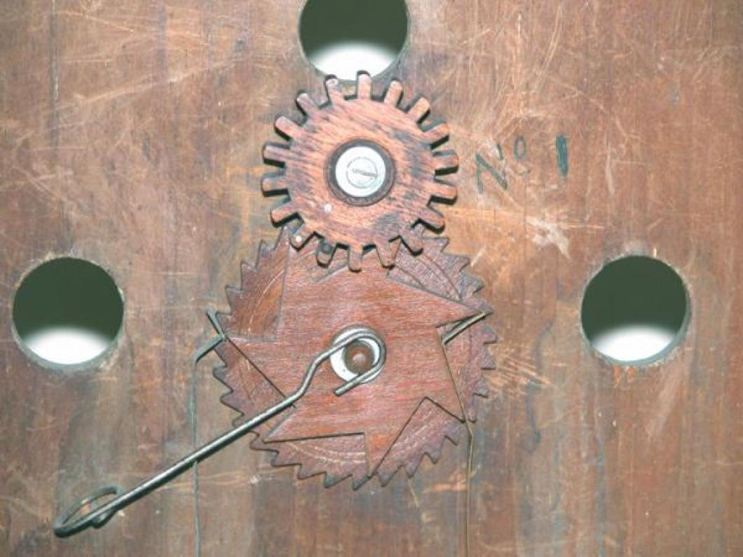 The calendar system drive gear (on the back of the main dial, two metal pins) for the 7 teeth day-of-the-week wheel and 31 teeth day-of-the-month wheel.  Note the edges of the two vertical metal-ribbon slip locks.