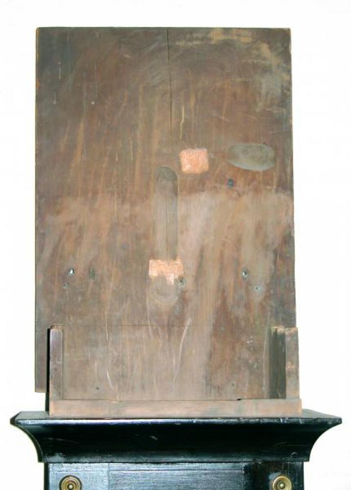 The inside surface of the upper back of the pine wood case.