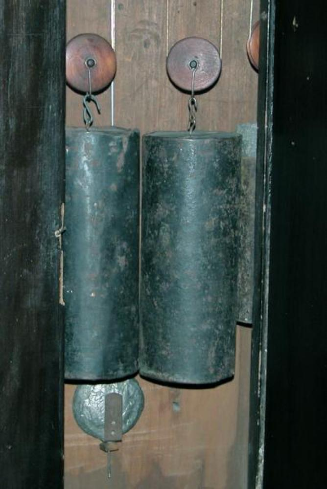 The three weights on their pulleys in the clock: the two large tin-can weights (stones inside) run the time and strike trains, the smaller partly visible lead weight runs the quarter hour bells train.