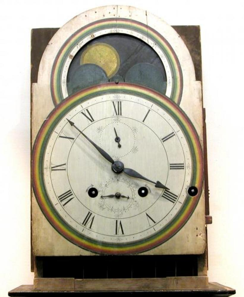 The clock's wood double dial with the hood off.