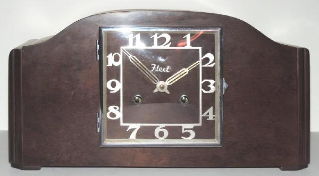 "A flat-topped ""humpback"" mantel clock with FLEET on the dial"