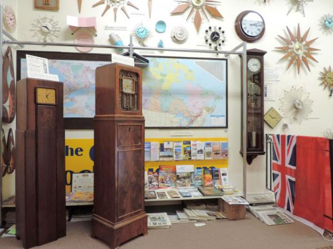Two 1930s electric floor clock radios in front of visitors homes Ontario and Canada wall maps.