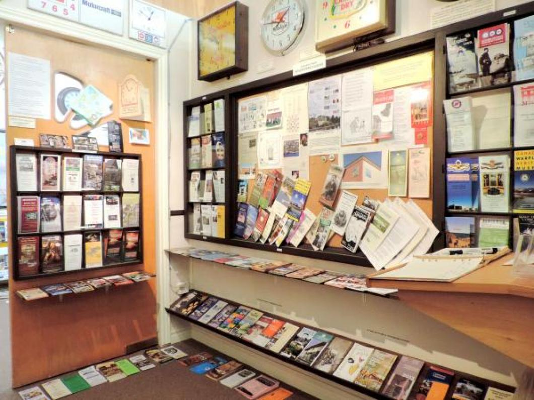 Racks of brochures for Renfrew County and Ontario museums (inside entrance to the Exhibit Room).