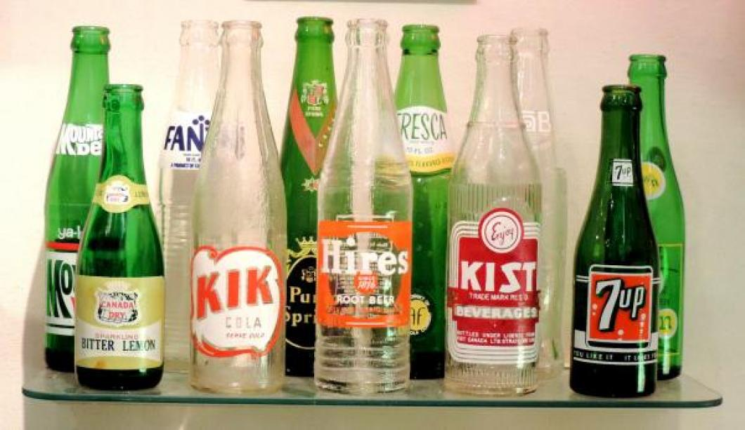 Some mid 20th century glass soft drink bottles that relate to advertising clocks for these products.