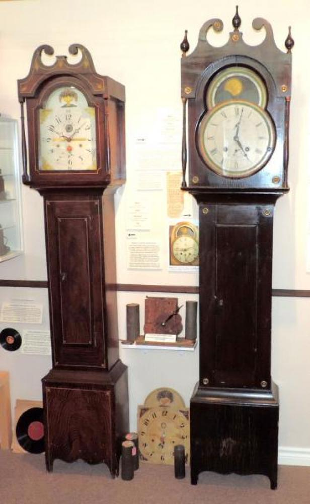 LEFT: 1820s Ira Twiss, Montreal, Lower Canada, burl walnut design on pine case, 30 hour wood movement, two tin-can weights, wood dial; RIGHT: assigned to Xavier Clement, early 1820s. north of Montreal, pine case, 8-day wood movement with calendar, three weights.